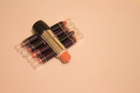 Small lipstick testers from different range of colors on pink background