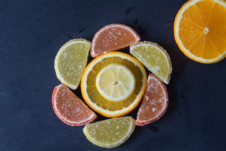 Colorful sugary marmalade like lemon and orange slices covered with sugar. Fruit jelly candies. Dolce vita. Closeup. Top view  on slate. Standard-Bild