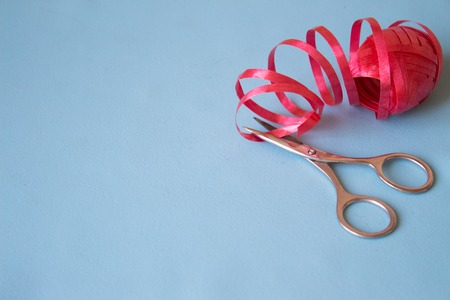 Scissors cut the red ribbon on blue background Stock Photo
