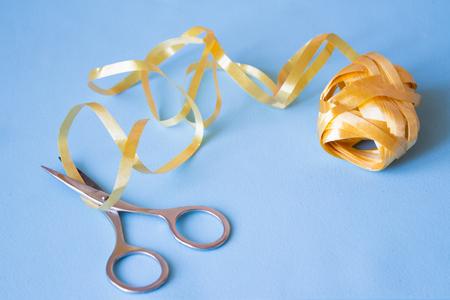 Scissors cut the yellow ribbon on blue background