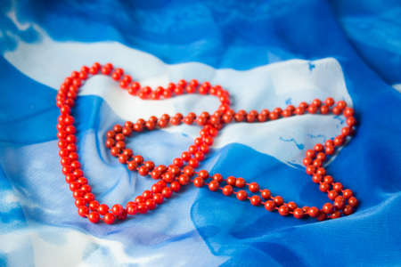 Two hearts of beads on a background of blue silk