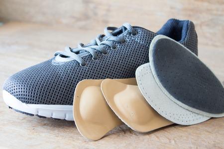 Chaussures de course gris avec semelles orthopédiques. Planche de bois