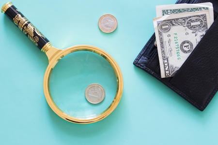 Magnifying glass and money on a neutral green background. ?op view. Stock Photo