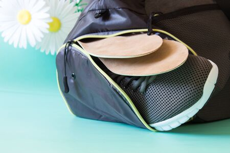Two pairs of orthopedic insoles in the pocket of a sports bag