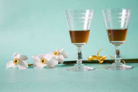 Two glasses of cognac or brandy and white daffodils on a neutral background, Romantic gift.
