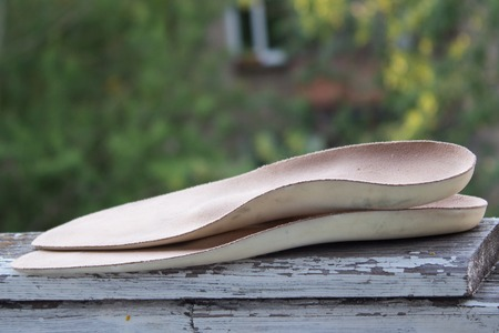 Leather orthopedic insoles on an old wooden board outdoors.