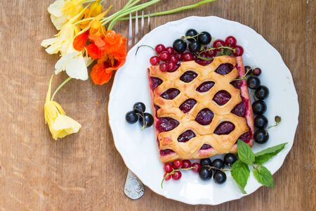 Cake with berry jam is served with fresh  red and black currant on a wooden table. Garden flowers nasturtiums. Top view.