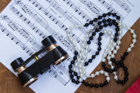 musical score: Black binoculars and necklace on music notes sheet. Trip to the theater. Top view. Stock Photo