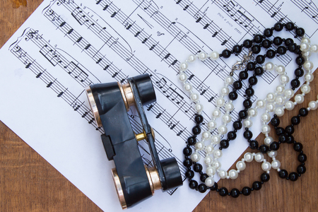 musical score: binoculars and necklace on background of music notes.