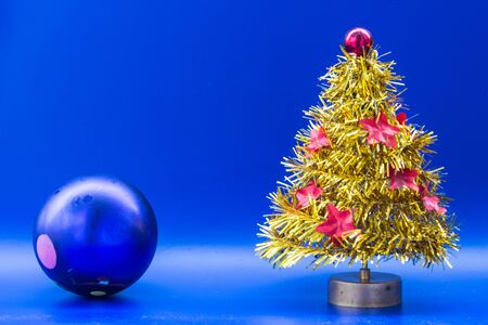 Yellow artificial Christmas tree decorated with red glittering asterisks,  blue New Year ball. Blue background