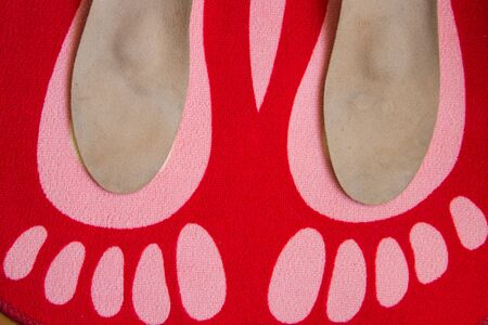 Leather orthopedic insoles are located on a red home carpet with the image of the feet Stock Photo