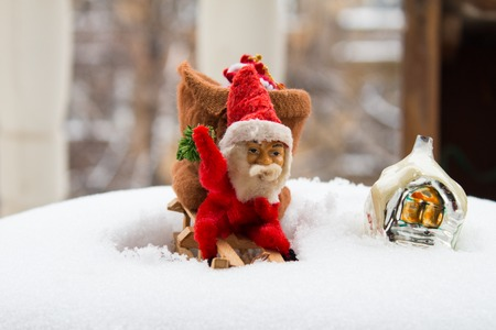 Vintage Christmas toys. Gnome on wooden sleigh and snow-covered house. Real snow background.
