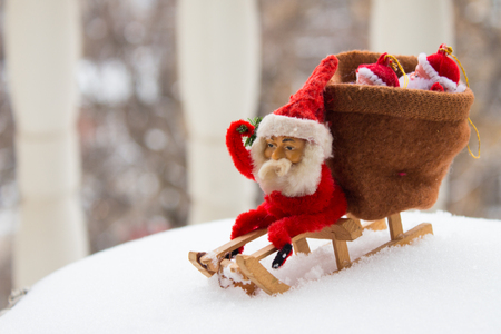 Christmas gnome sits on wooden sled with bag of gifts behind him. Real snow background. Vintage toy Stock Photo