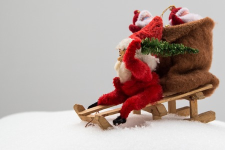 Gnome in red clothes with bag of gifts and christmas tree in your hand. Wooden sled on real snow. Vintage toy.