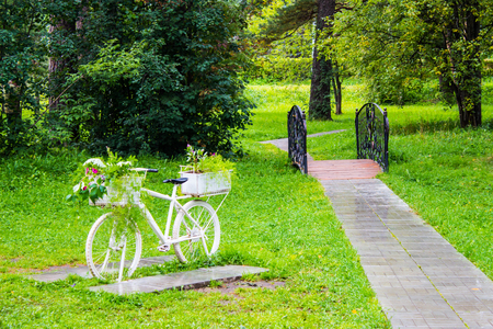 Vintage white bicycle with baskets of flowers among the garden. Beautiful decoration on natural background. Stock Photo
