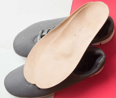 Orthopedic insoles and sports shoes on red - white background. Prevention of orthopedic foot diseases, foot care. Archivio Fotografico - 150760308