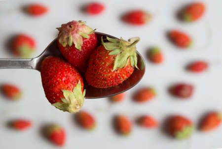 Strawberries in a wooden spoon on blurred background of berries. Top view.