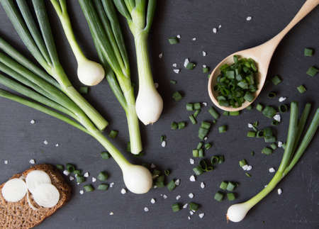 Pile of green onion and herb chopped in wooden spoon. Stone background. Top view.