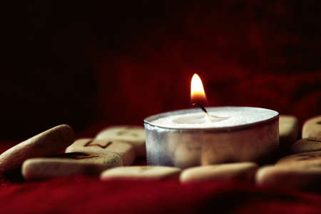 fortunetelling: Runes with pouch and candle on the fur