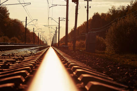 sun track: junction of railways track in trains station against  beautiful light of sun set sky use for land transport and logistic industry background ,backdrop,copy space theme Stock Photo