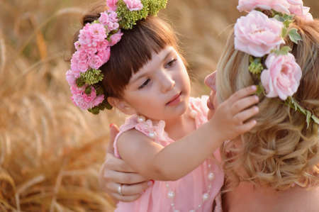 corrects: The daughter and mother look at each other, the daughter straightens the wreath of roses on her head Stock Photo