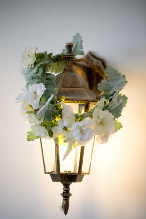 wall sconce: Golden sconces lantern with wreath. Warm and cozy light Stock Photo