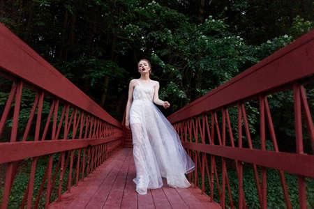 Young girl walking in a flowing dress on the red bridge.