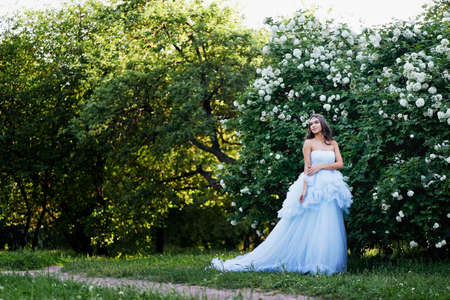 lush: Gorgeous brunette in a lush blue dress with her hair is set in a lush garden