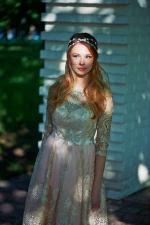 pleasantness: Beautiful girl in bright lace dress stands in the shade of the trees, the light falls on the face. The light spot Stock Photo