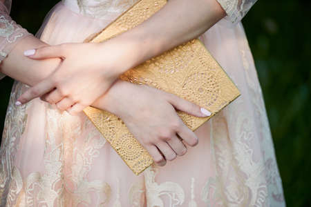 pleasantness: Female hands holding gift box. On the background of the lace dresses