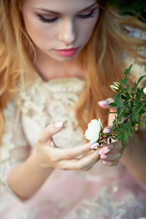 pleasantness: Beautiful girl in a light dress holding a rose on a branch. Tenderness