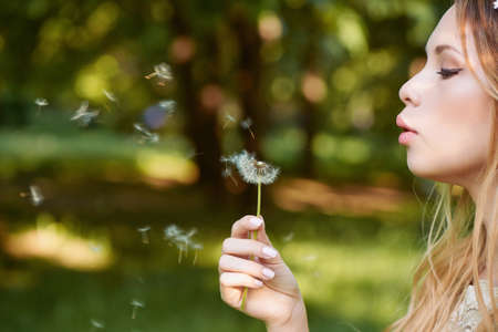 pleasantness: Girl blowing on a dandelion, ease and tenderness. the smile on the face