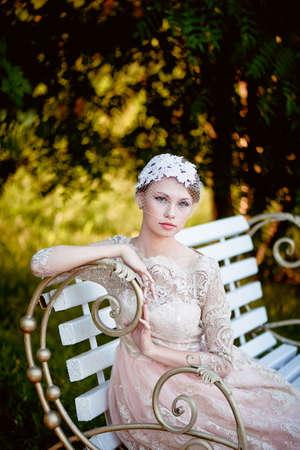 pleasantness: Beautiful young blonde with a hairstyle and veil sitting on a bench, romantic looks