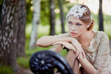 restraint: Beautiful young blonde with a hairstyle and veil sitting on a bench, romantic looks