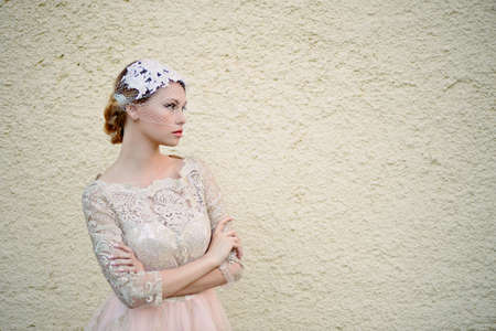 pleasantness: Beautiful young blonde with a hairstyle and veil is against a background of solid sand wall, neutral colors, pastel and romantic looks Stock Photo
