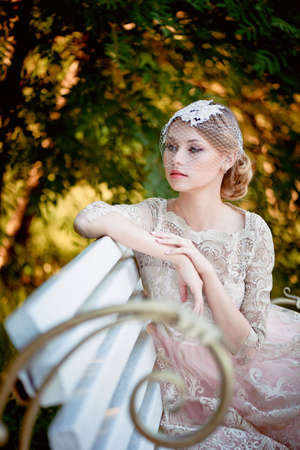 restraint: Beautiful blonde with a hairstyle and veil sitting on bench, romantic looks