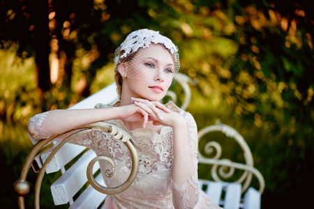 pleasantness: Beautiful blonde with a hairstyle and veil sitting on bench, romantic looks
