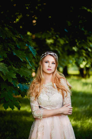 pleasantness: Pretty young tender blonde in a lace cream dress against the background of a garden