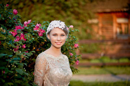 restraint: Pretty young tender blonde in a lace cream dress against the background of a blooming garden