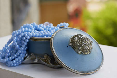 Blue jewelry Box with the silver moldings on the legs, with blue beads on a string. Close, bokeh