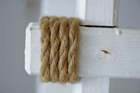 coiled rope: The rope is coiled around a white wooden support chair Stock Photo