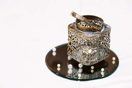 mirrored: A Golden candlestick with a candle on a mirrored stand and beads. Decoration of wedding table
