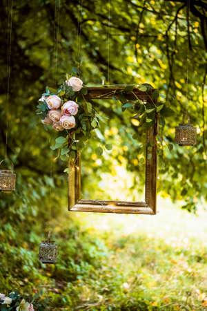 Alter goldener Rahmen, verziert mit Blumen, hängend an einer Niederlassung auf grünem Hintergrund. Blumendekor für Hochzeit Foto-Shooting