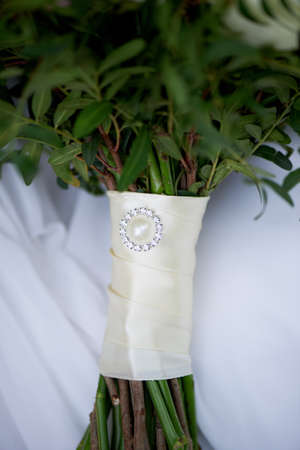 tightly: Leg wedding bouquet tightly laced in satin ribbon with a brooch. Floral Stock Photo