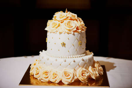 tiers: Elegant white wedding cake with cream roses in 2 tiers Stock Photo