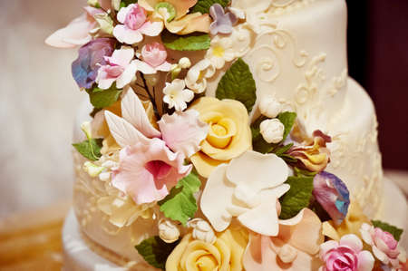 tiers: Gorgeous cream wedding cake with cream roses in 2 tiers with flowers from mastic Stock Photo