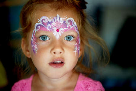 Pretty exciting blue-eyed girl of 2 years with a pink face painting Standard-Bild