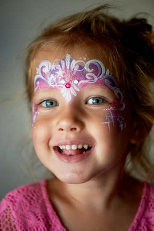 Pretty exciting blue-eyed girl of 2 years with a pink face painting Stock Photo