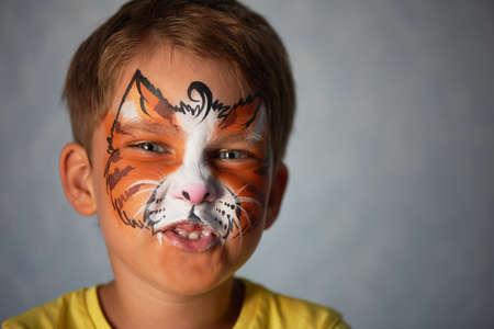 6 jaar oude jongen met blauwe ogen, met schminken van een kat of een tijger. Oranje.