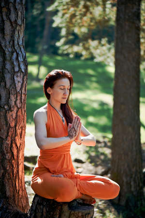 Young beautiful red-haired girl does yoga in Park on green background. Relaxation.